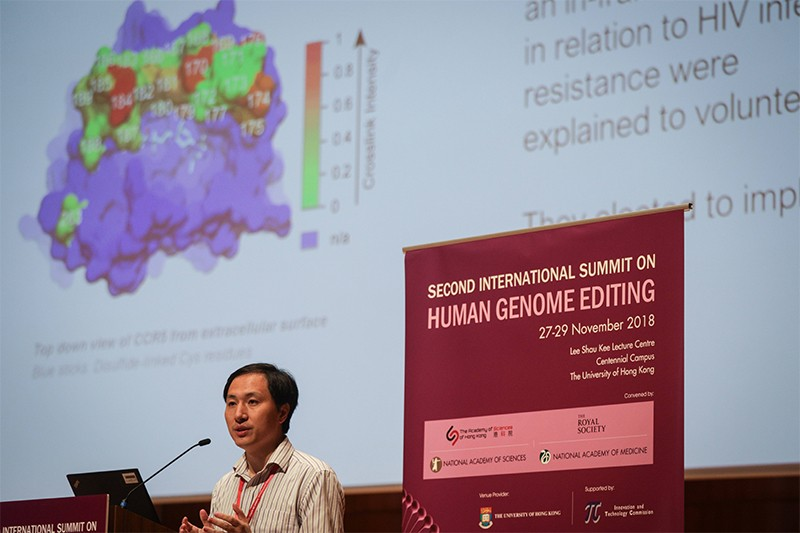 He Jiankui talks at the Human Genome Editing summit in Hong Kong. Behind him is a slide showing a CRISPR CAS molecule