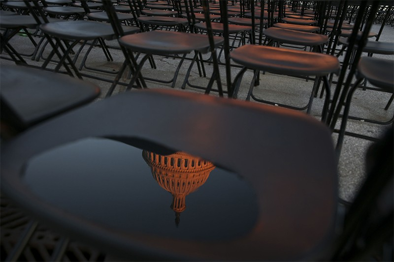 U.S. Capitol building is reflected in a water puddle on a chair arranged for an audience