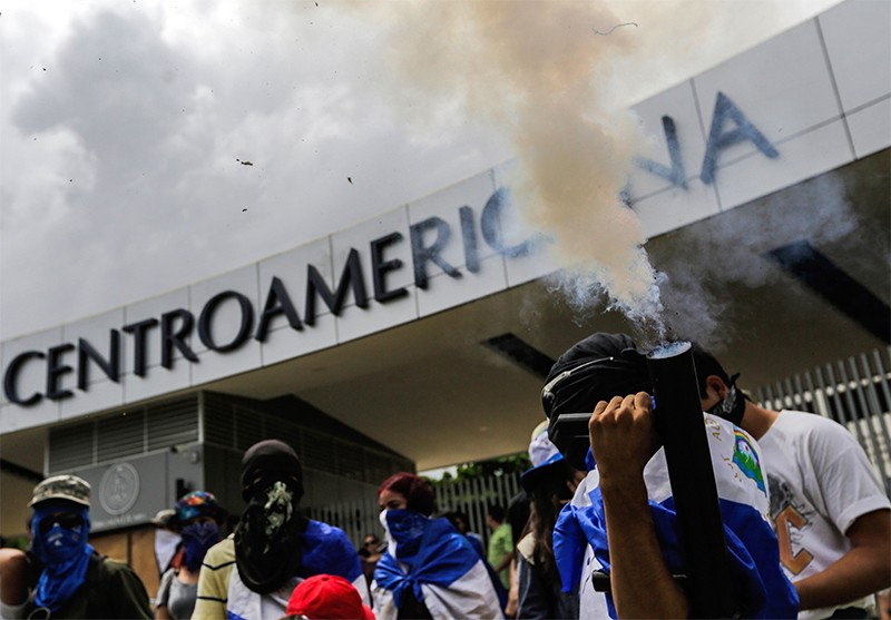A student fires a hime made mortair during a student protest outside UCA in Nicaragua