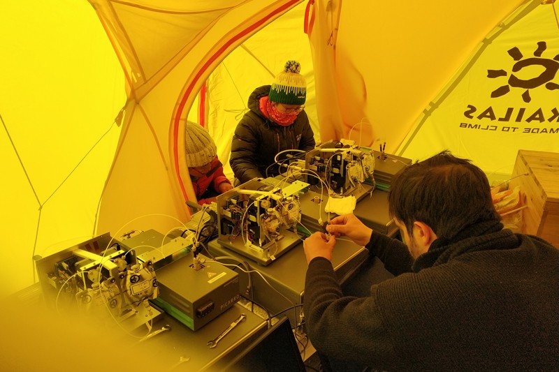 Researchers set up instruments in a tent