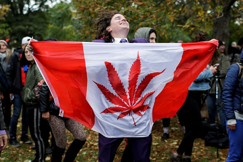 A man dances with a marijuana flag