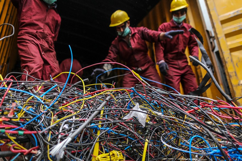Workers offload cables at an electric recycling facility