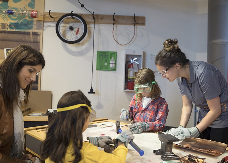 Scientists and girls using tools in science center workshop