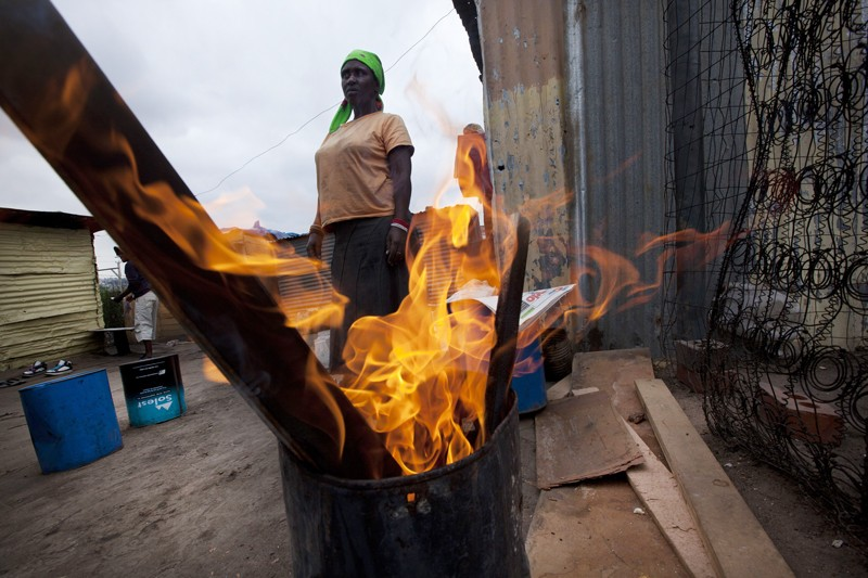 Women burns wood for fuel in Soweto Johannesburg