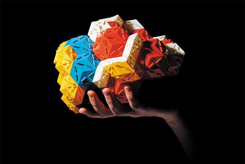 A hand holding a colourful quasicrystal model. Simon and Schuster.
