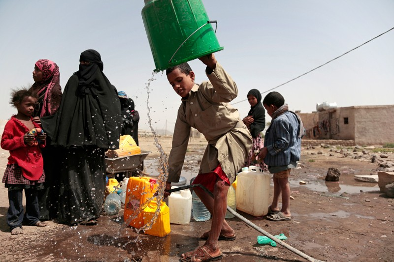 Boy collects water in Yemen