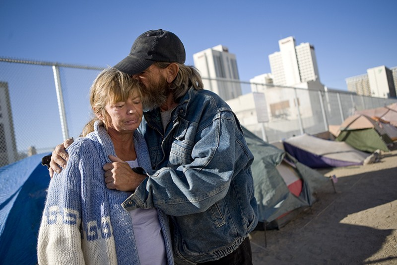 A couple hugs in in a tent city for the homeless in downtown Reno.