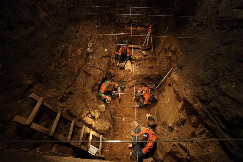 4 scientists digging Pleistocene deposits in Eastern room of Denisova Cave, 2010. 4 scientists. Pleistocene deposit in Eastern room of Denisova Cave, 2010.
