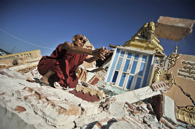A monk clears debris off of a destroyed Pagoda on November 12, 2012 in Myanmar.