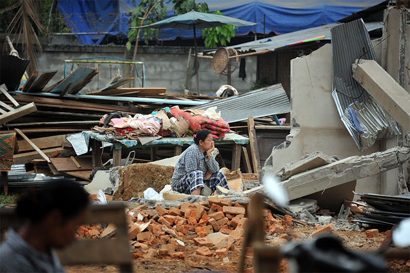 An earthquake survivor sits amid destroyed houses and rubble in Tarlay, Myanmar, in 2011.