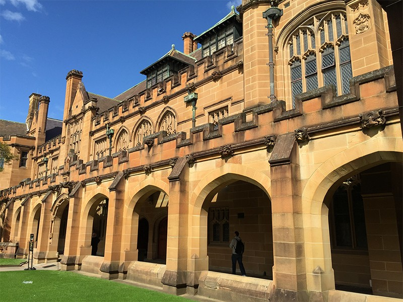 A student walks in the shadows of the Quadrangle arches at the University of Sydney