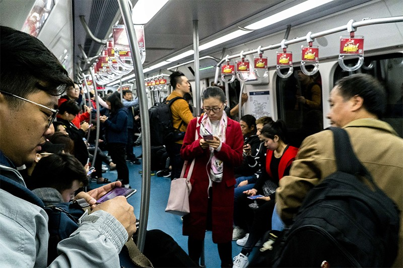People are watching smartphones on a busy subway car in China