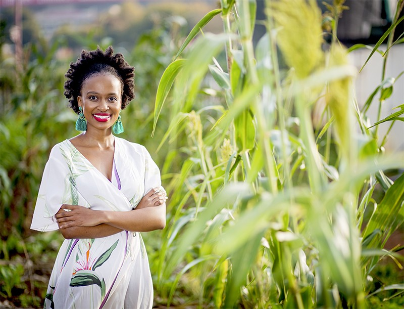 Nodoni Mcunu photographed outside among some plants.
