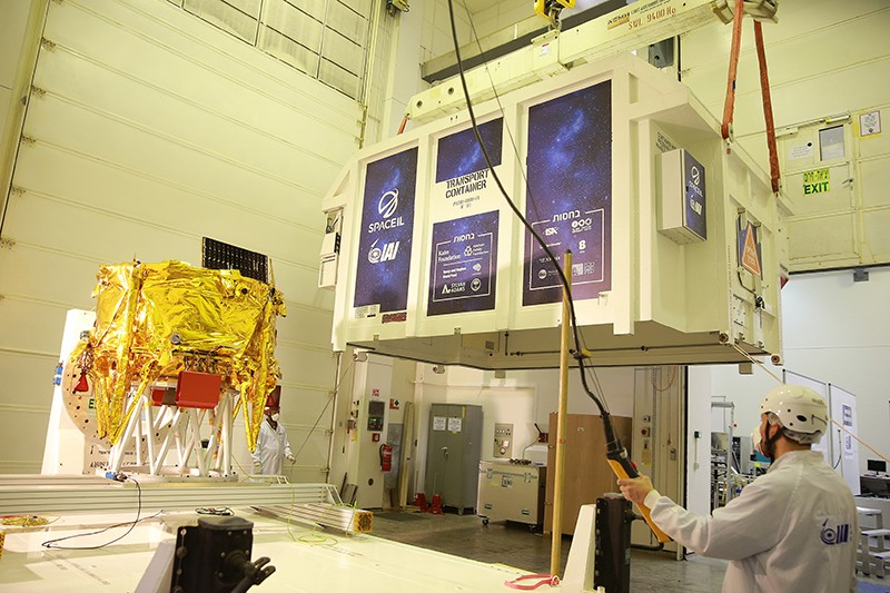 A man wearing safety gear uses an automated system to hoist a lander draped in gold foil into a container.