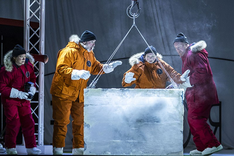 Four opera singers on stage, dressed in Arctic gear, crowd around a block of ice.
