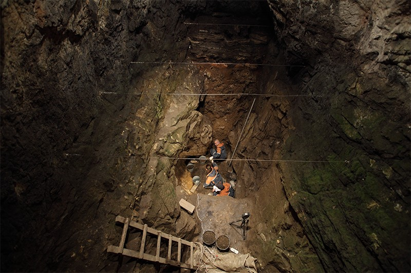 Scientists excavating hominin remains in the east chamber of the Denisova Cave in the Altai Mountains, Russia