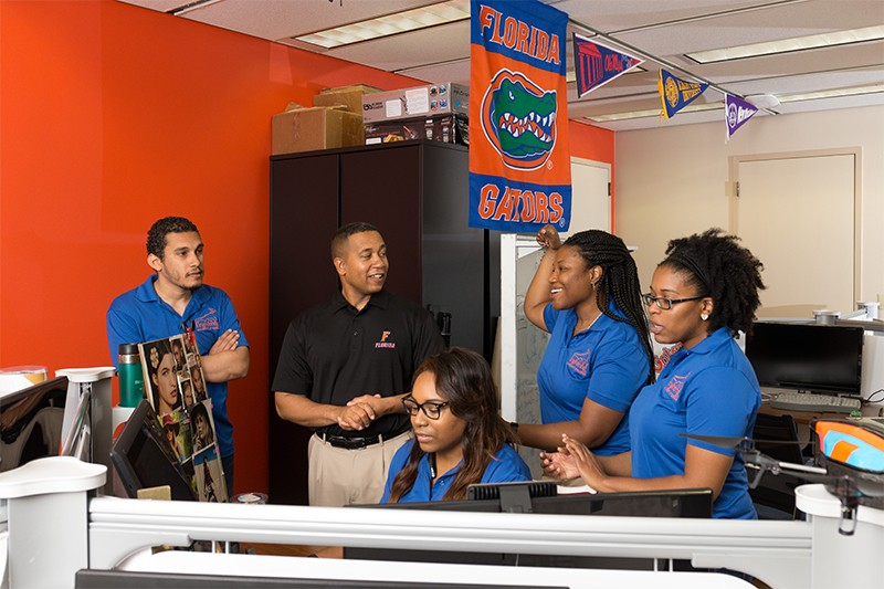 Professor Juan Gilbert (second from left) interacts with his team in their workroom the University of Florida
