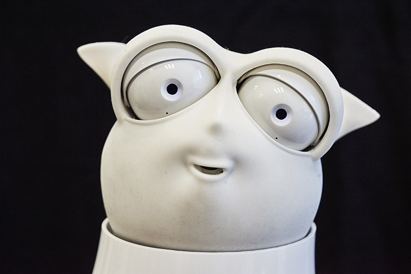 The head of a white robot with a chubby face, pointy ears and bulbous eyes, against a black background.