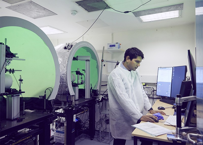 Dr Aman Saleem looks at results on his computer, with custom virtual reality (VR) dome setups on his left
