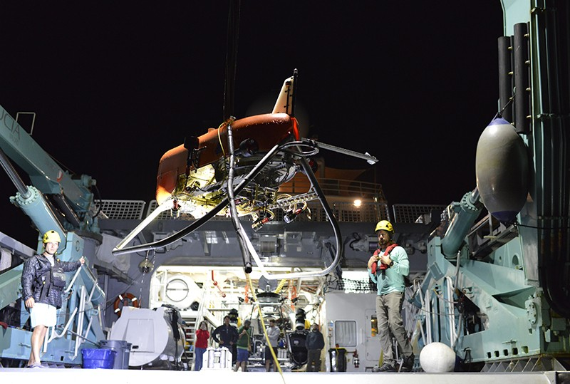 WHOI's new AUV Orpheus is lowered into the ocean from the ship Alucia to search for undiscovered sea life