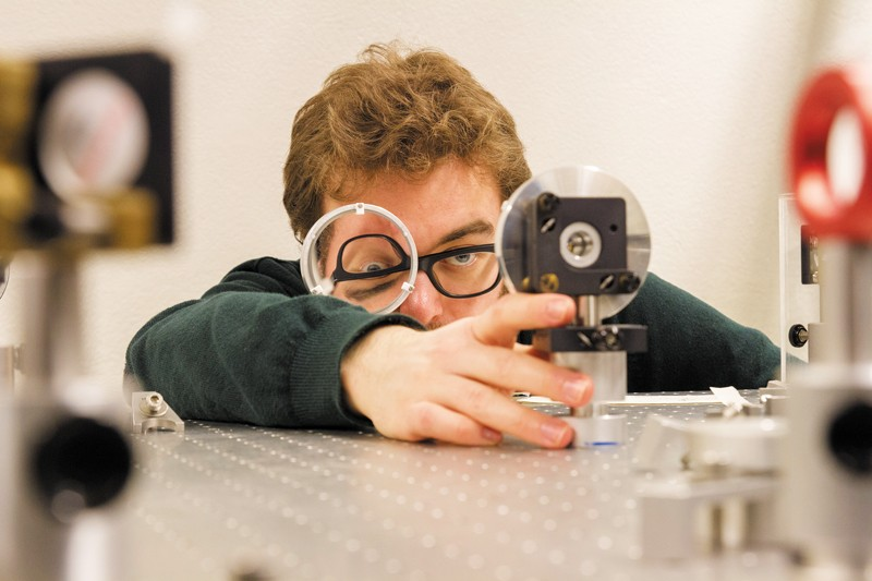 Researcher aligns spherical silver mirrors on the laser table