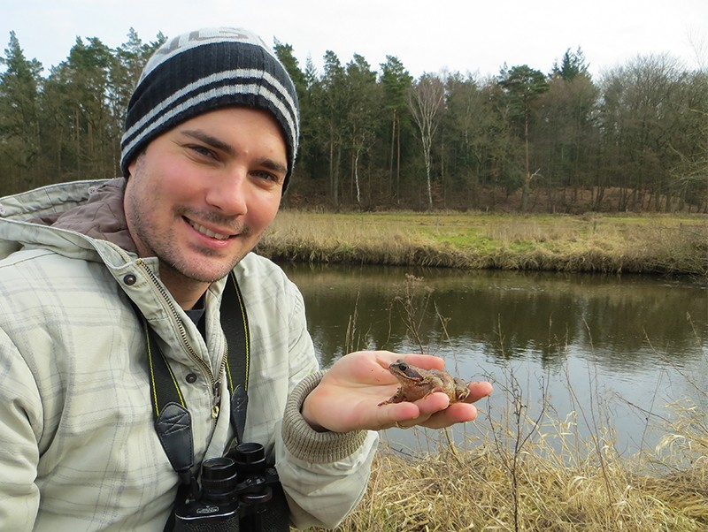 Dale Nimmo holding a frog by a lake