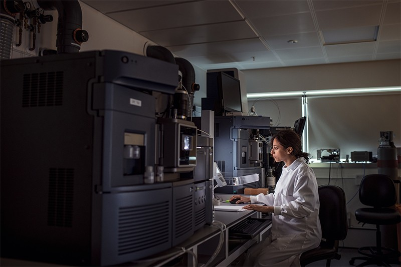A female biochemist looks worriedly at a computer screen in a dimly lit laboratory