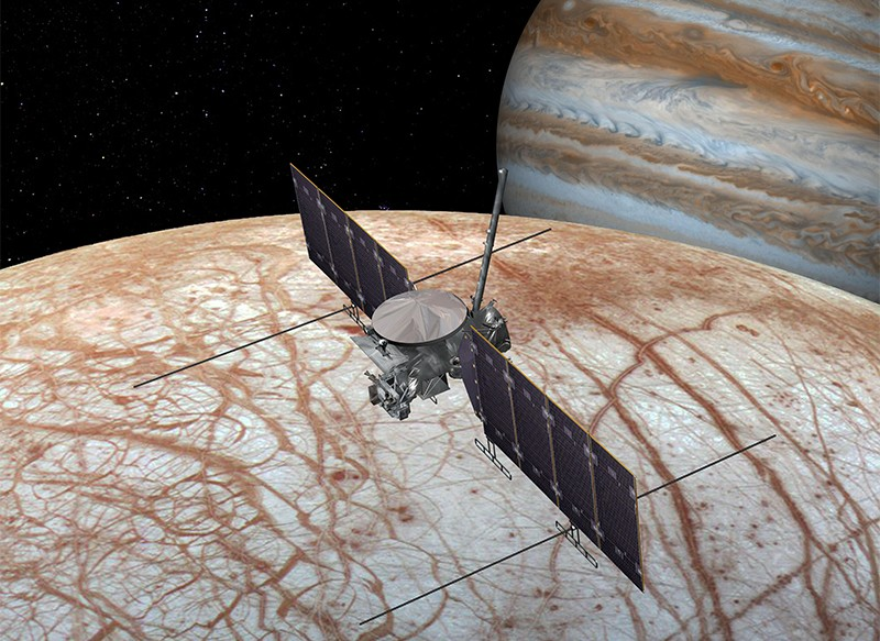 Artist's rendering showing NASA'S Europa Clipper spacecraft flying over the moon's surface with Jupiter in the background
