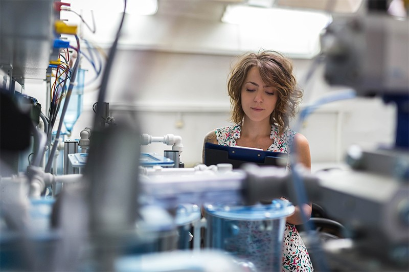 A female scientist examines printed data whilst working on machines in a laboratory