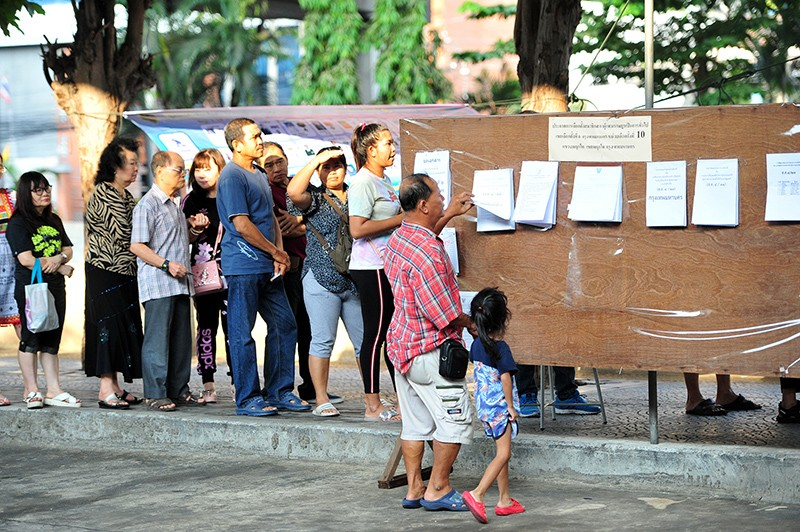 Thai people queue to cast ballots at a polling station in Bangkok, Thailand