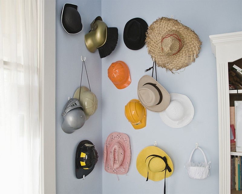 Collection of different hats hanging on a wall