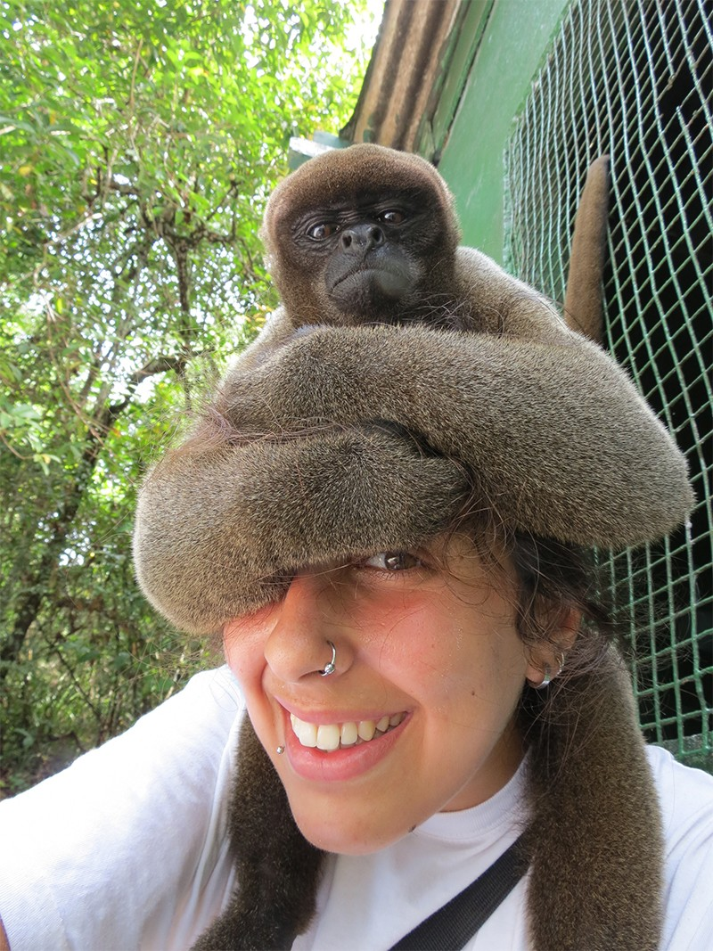 A woolly monkey sits on the head of Bárbara Cartagena Matos in the Amazon