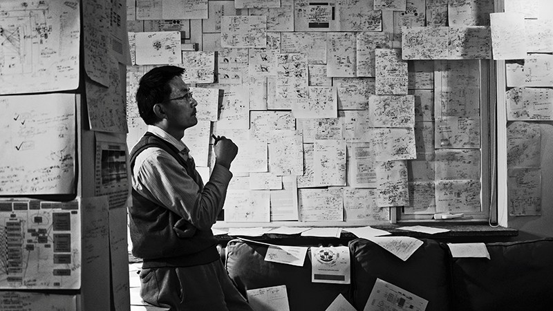 A scholar studying information posted on the walls of an office