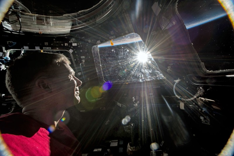 An astronaut looks through the window on the space station at the Sun rising over Earth