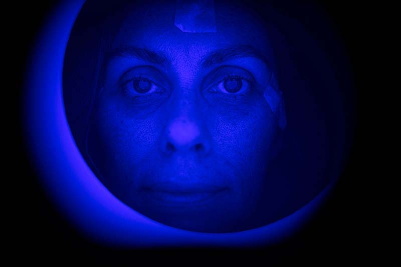 A human face bathed in deep blue light