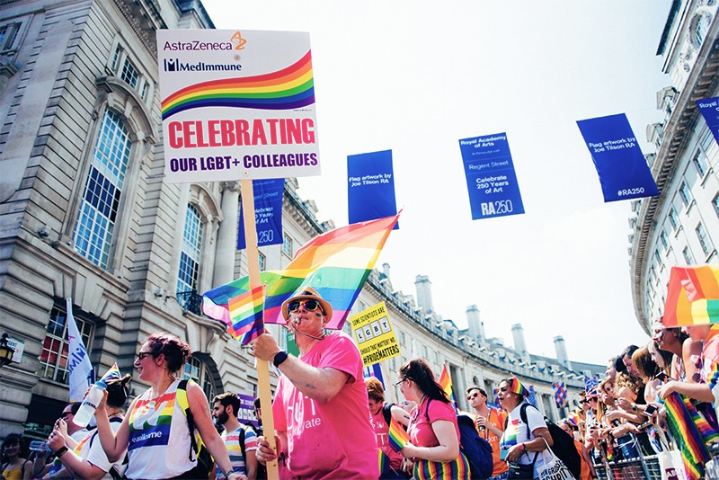 Neil Reavey holds a sign celebrating LGBT+ colleagues while marching with AZplus and PSA in Pride, London