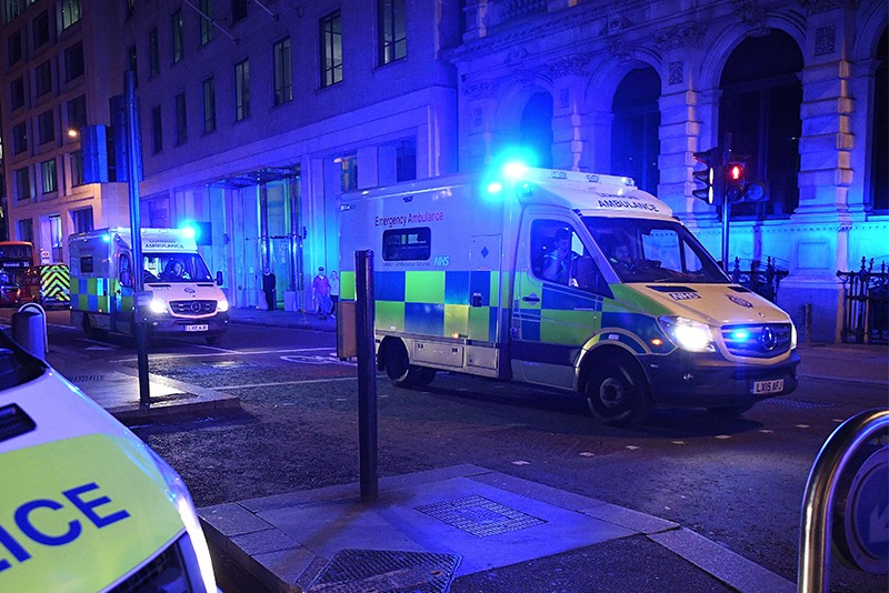 Ambulances head north from London Bridge at night.