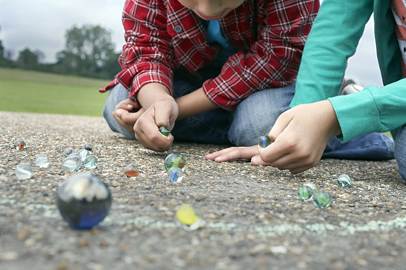 Children playing marbles in a playground