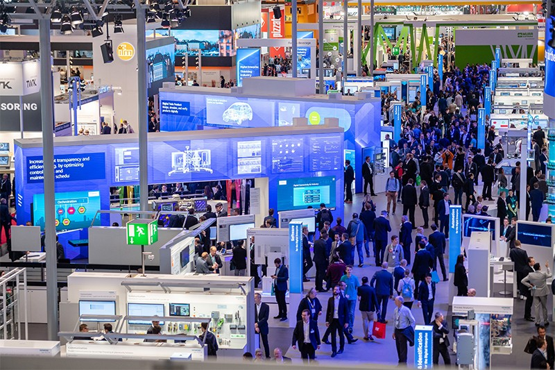 Visitors walk past booths at the Hannover Industry Fair in 2019. The main focus of the fair is AI and 5G.