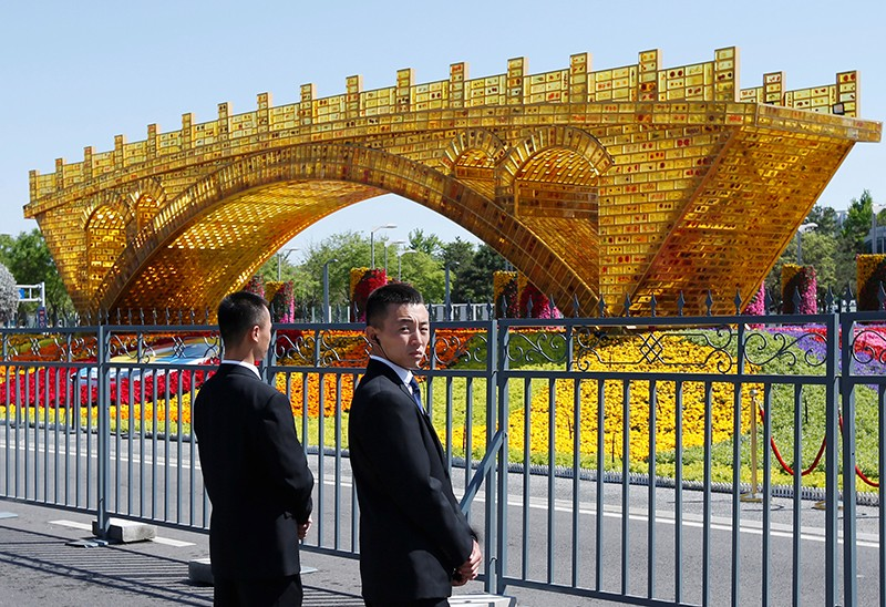 "Security personnel stand guard near a ""Golden Bridge on Silk Road"" decoration for the Belt and Road Forum in Beijing, China"