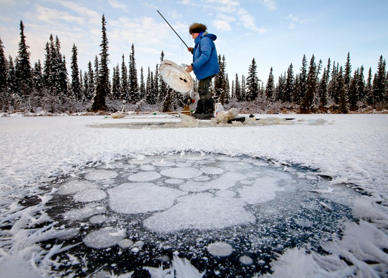 Scientist conducting research on a frozen lake with a collection of methane under the ice