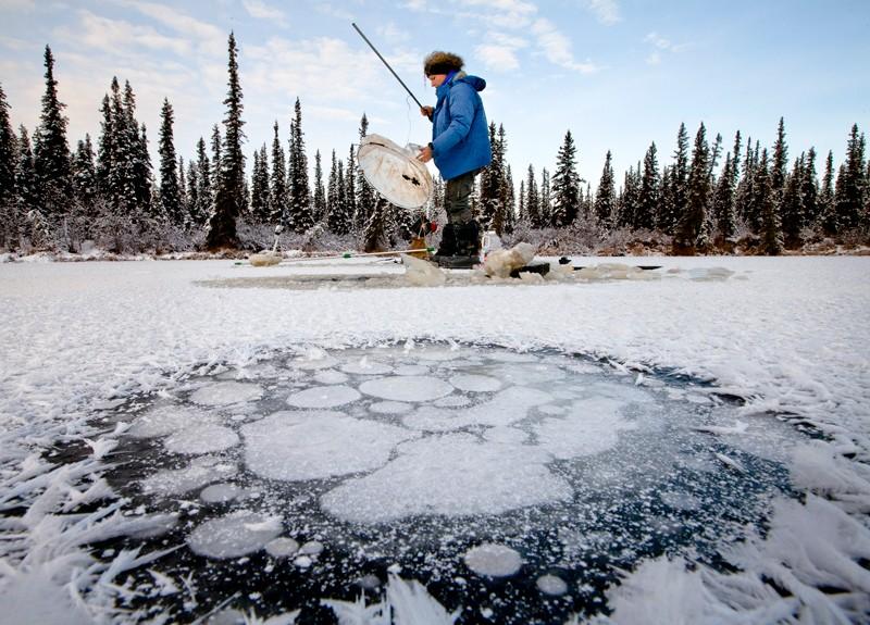Uno scienziato conduce ricerche su un lago ghiacciato con il metano che si raccoglie sotto il ghiaccio