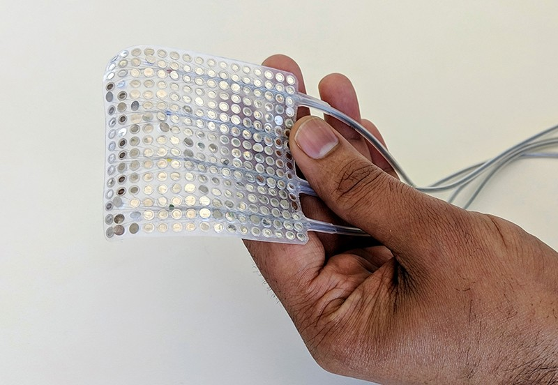 A hand holding an array of intracranial electrodes: a palm-sized sheet of plastic studded with metal, attached to wires.