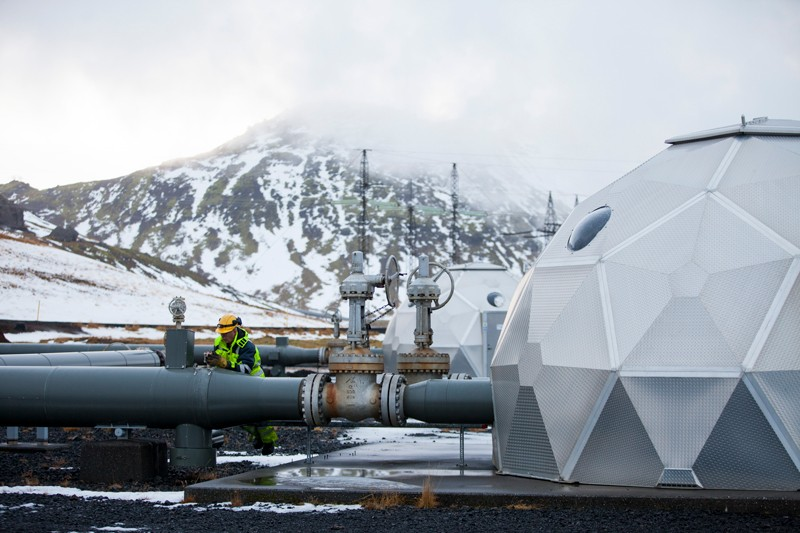 A man works on a pipe beside a carbon injection site well near Reykjavik Energy's Hellisheidi Geothermal Power Plant