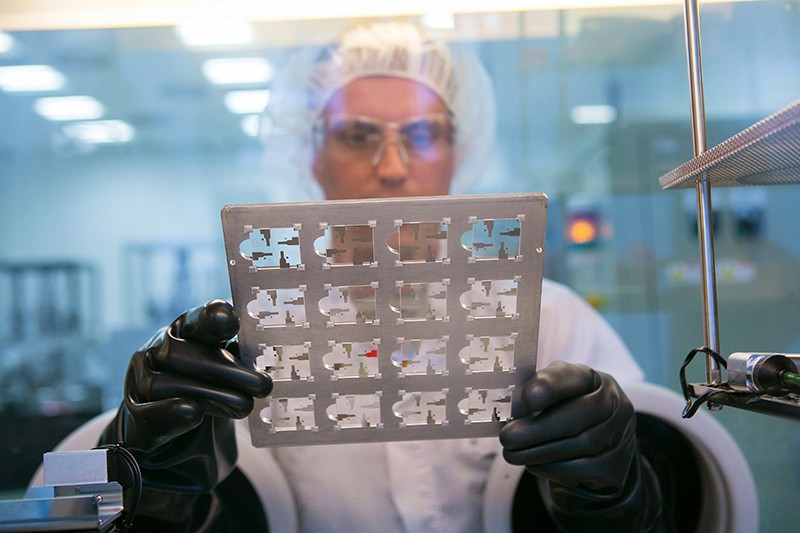 A technician holds a sheet of pre-coated OLED test cells in a laboratory