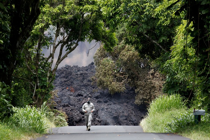 A figure in protective clothing walks on a road in front of the lava flow from the the Kilauea Volcano