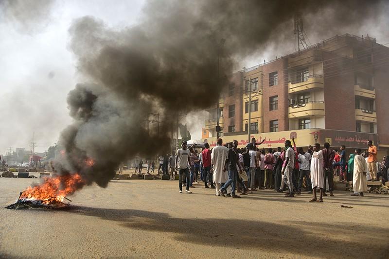 Des manifestants soudanais passent devant des pneus enflammés lors d'une manifestation dans la ville jumelée d'Omdurman, à Khartoum, le 3 juin 2019