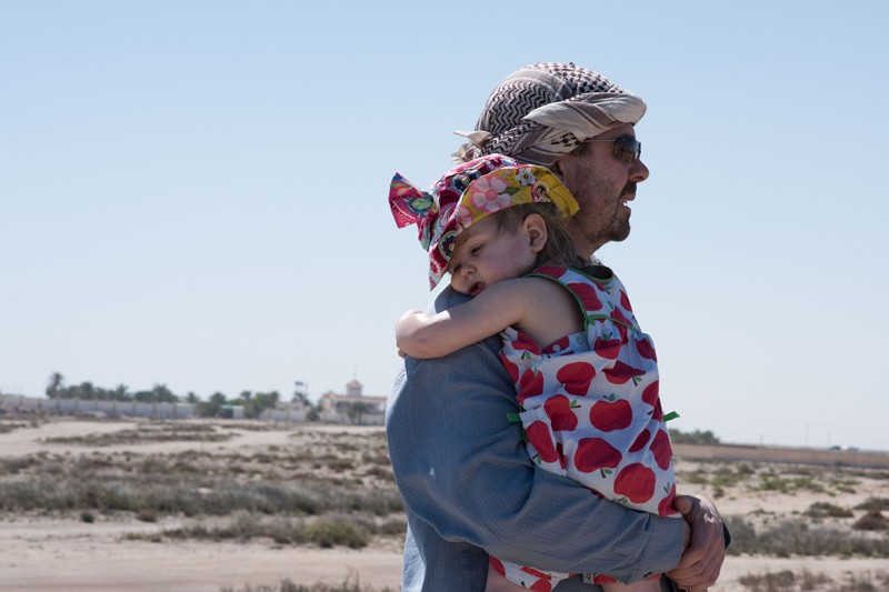 A father carries his young daughter across a desert landscape