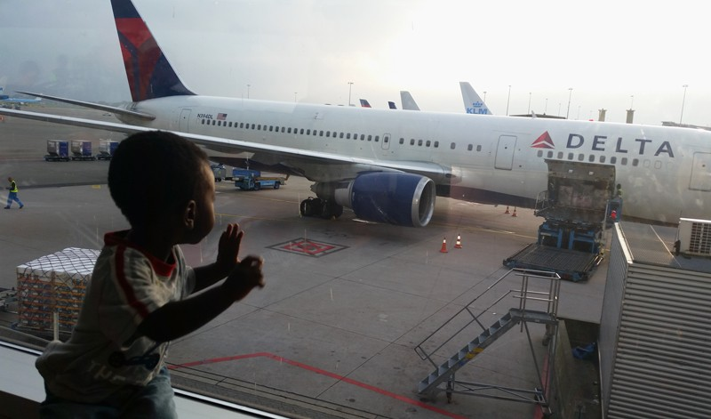 A toddler looks out the window of an airport at a plane destined for Uganda