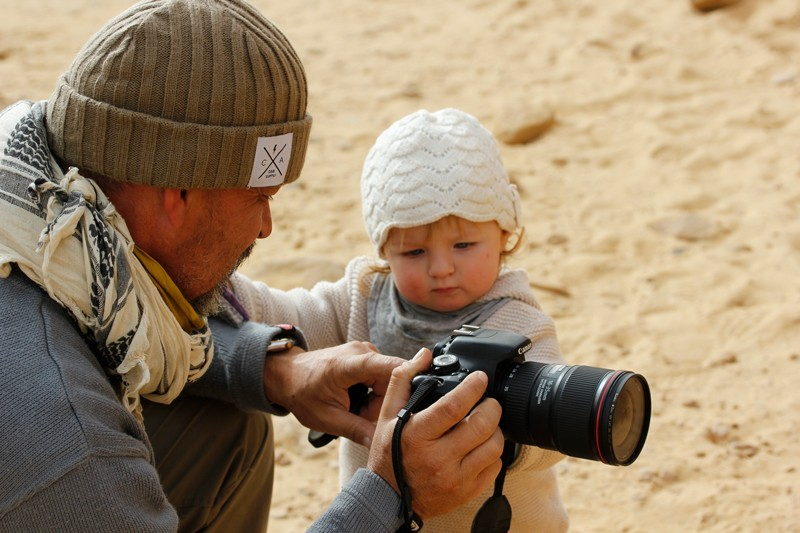 A researcher shows his young daughter how to use a camera